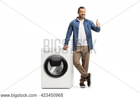 Young man standing next to a washing machine and showing thumbs up isolated on white background