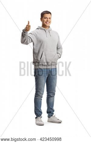 Full length portrait of a young man in a gray hoodie and jeans showing thumbs up isolated on white background