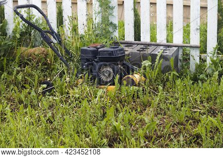Abandoned And Partly Disassembled Garden Power Equipment Next To A Fence