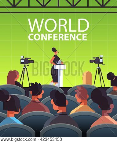 Businesswoman Giving Speech At Tribune With Microphone On Corporate International World Conference