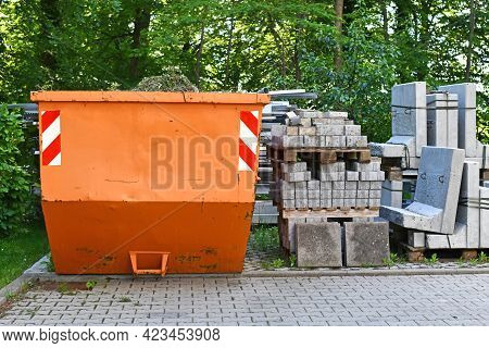 Orange Industrial Transportable Dumpster Container And Cobble Stones On Palette At Construction Site