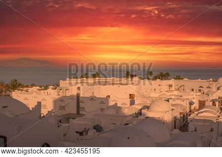 Fabulous Mysterious White Old Arab City Under The Red Dramatic Sky Sunset. Aerial View. Roofs And Do