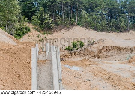 Concrete Aqueduct Set In Hillside At New Construction Site With Treeline In Background.