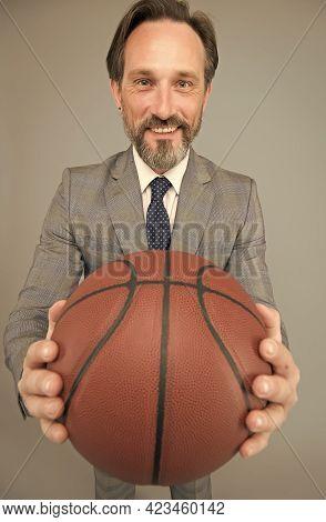 Coach Career Paths Start Here. Basketball Coach Grey Background. Business Coach Hold Basketball Ball