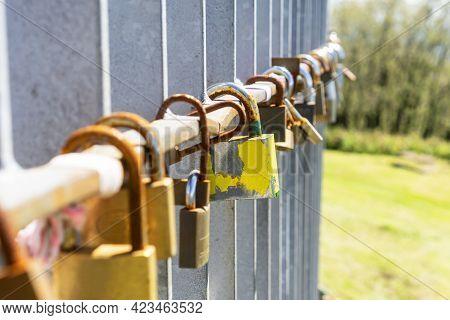 Old Rusty Love Padlocks Hanging On Railing Outdoors. Close Up. Symbol Of Loyalty