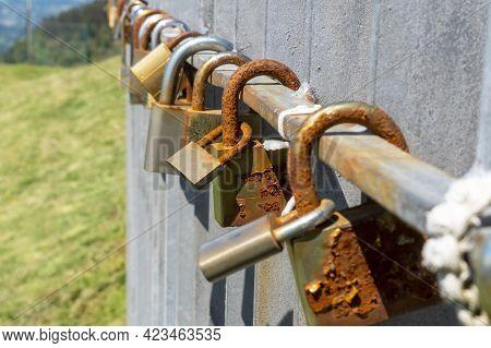 Old Rusty Love Padlocks Hanging On Railing Outdoors. Close Up