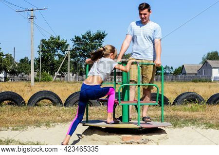 Defocus Emotion Preteen Girl Riding A Carousel On Playground With Young Man, Guy, Older Brother Or F