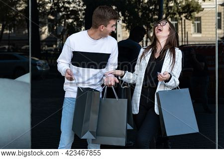 Young Loving Couple Carrying Shopping Bags And Laughing. Mock Up. Black Friday. Shopping. Consumeris