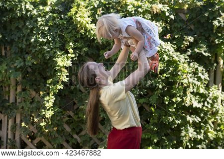 Mom Throws The Baby Into The Air. Mother Circles Child In Her Arms. Portrait Of Happy Mommy And Kid