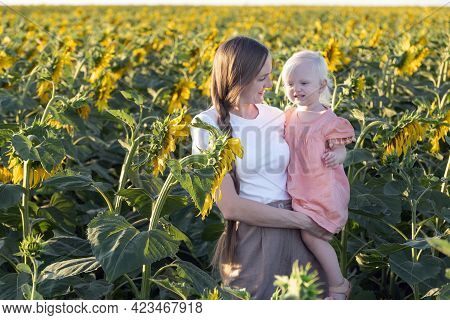 Happy Mom And Daughter In Sunflowers Field. Tenderness And Care.
