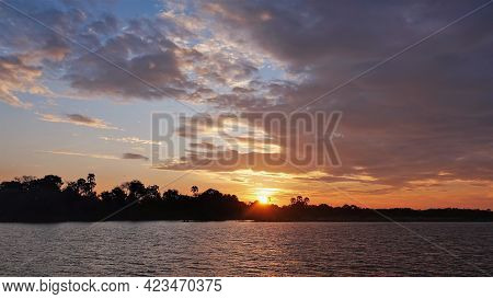 Bright Sunset Over The River. Lilac Clouds In The Blue Sky. The Sun Is Shining Over The Jungle. Refl