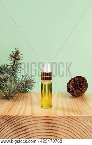 Aromatherapy And Spa Concept With Of Essential Spruce Oil In Small Glass Bottle, Twig, Cone On Woode