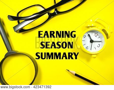 Finance Concept.text Earning Season Summary With Glasses,magnifying Glass,pencil And Alarm Clock On