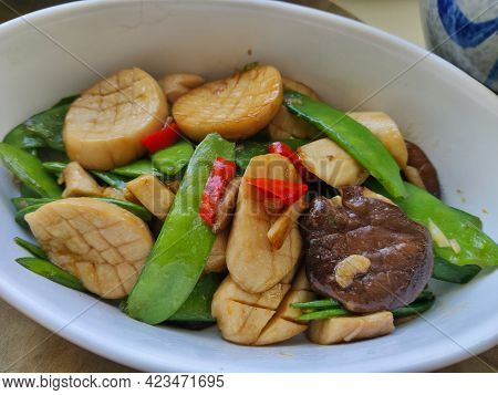 Closeup Look On A Dish Made Of Shiitake Mushrooms, Pea Hulls, And Red Chili Pepper. It's Served In A