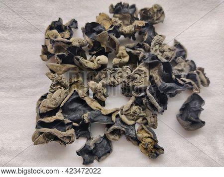 Detail Of Dried Black Jew's Ear (wood Ear) Mushrooms Sitting On The White Table Cloth. The Mushroom