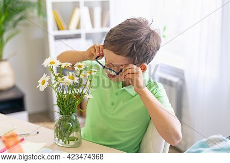 Inquisitive Smart Boy Through Glasses Examines A Bunch Of Daisies, Sitting At Table At Home. The Chi