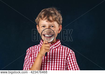 Funny Child With A Magnifying Glass Near His Mouth On A Black Background. The Boy Shows His Teeth Th