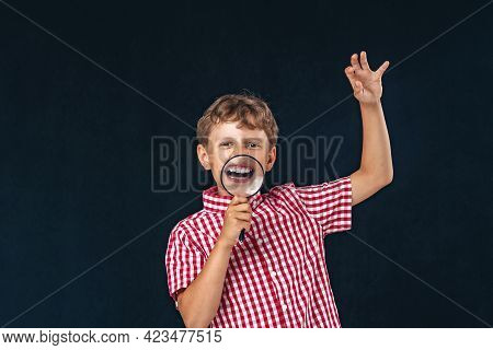 Cheerful Child With A Magnifying Glass At Mouth, Frightening On A Black Background. Boy Shows His Te