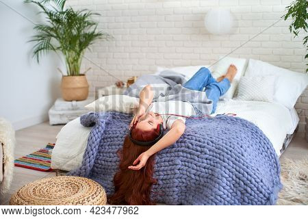 Portrait Of A Beautiful Smiling Young Woman With Headphones, Lying In Bed And Listening To Music. Th