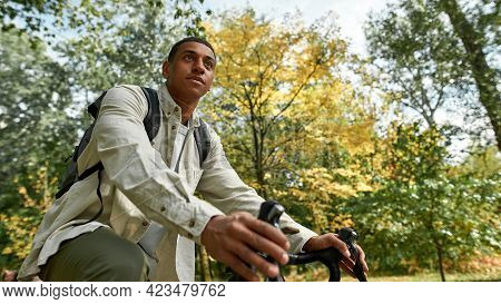 Young African American Man With Backpack Riding Bike In Spring Nature, Bottom View. Work In Nature C