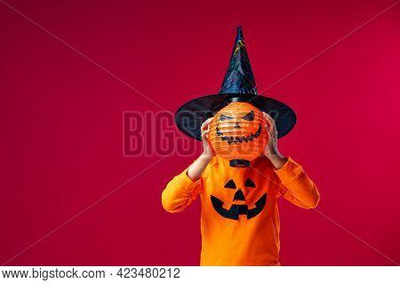 Happy Halloween! Frightening Children's Costume With Pumpkin Jack Instead Head On Green Background.