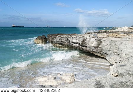 The View Of A Rocky Eroded Coastline With Wave Splashes On Grand Bahama Island And Industrial Ships