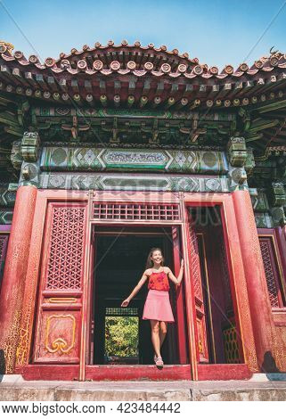 China travel vacation mixed race Asian Caucasian tourist woman visiting old chinese temple walking through traditional entrance door at sightseeing destination. Multiracial girl tourist. Vertical.