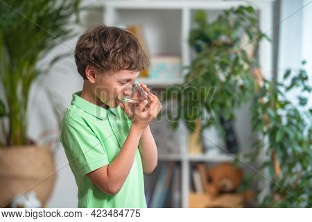 Cute Little Boy Drinking Water In Kitchen At Home. Child Holds Glass Clean Filtered Drinking Water I