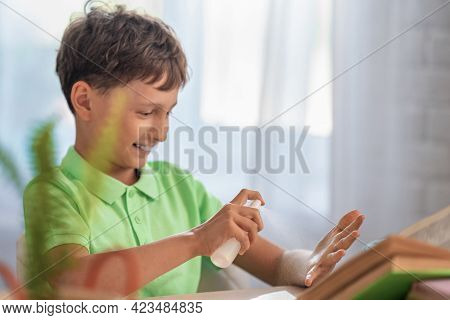 Happy Boy Sprays Disinfectant Alcohol Spray On His Hands To Protect Them From Viruses During Epidemi
