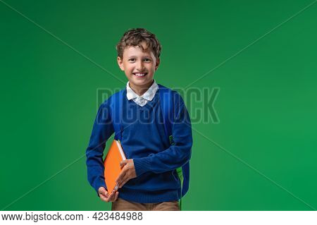 Mischievous Laughing Schoolboy Of 7 Years In Uniform Is Holding Book And Backpack. Isolated On Green