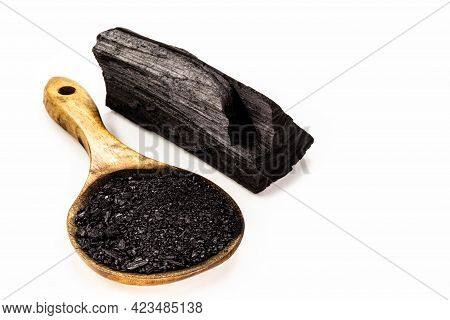 Rustic Wooden Spoon With Activated Powdered Charcoal, With Pieces Of Charcoal In The Background, Iso