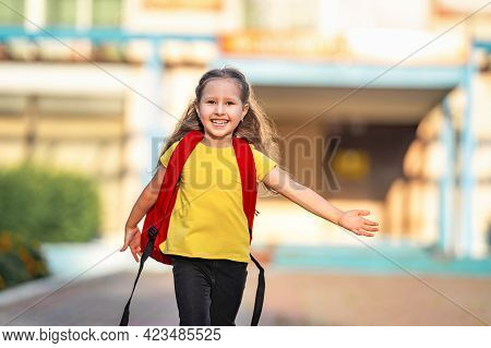 Schoolgirl Elementary. Little Girl With Backpacks Runs From School. A Happy Child Is Happy To Return