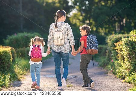 Mother Accompanies Students On Road. Children With Briefcases Walk From School, Holding Their Mother