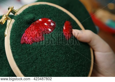 Womens Hand Embroidery Mushroom Hat In Hoop On Dark Material. Close-up. Concept Of Needlework, Hobby