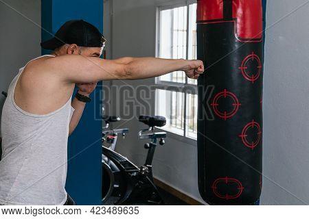 Man Punching Punching Bag In Gym. Gym.