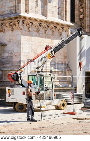 Milan, Italy - July 7, 2020. Construction Worker On Duty Standing Close To Crane. Duomo Cathedral Bu