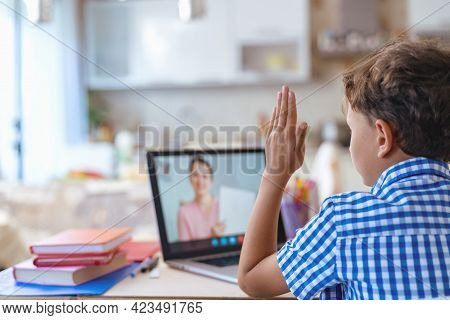 A Focused Schoolboy Boy Uses A Laptop For Distance Learning During The Quarantine Period. The Child