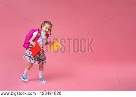 Back To School! Cute Hardworking Kid In Uniform Jogging On Pink Background. Child With Backpack. Lit
