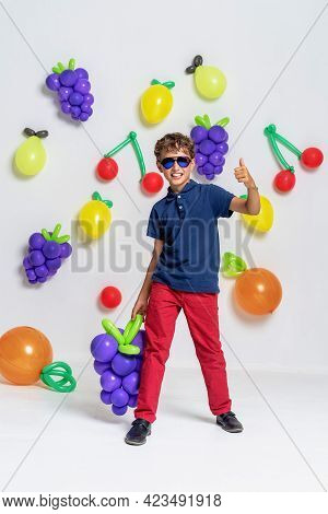 Stylish Boy In Sunglasses, Fashionable Clothes Stands And Poses On Fruit Background In Studio. Child