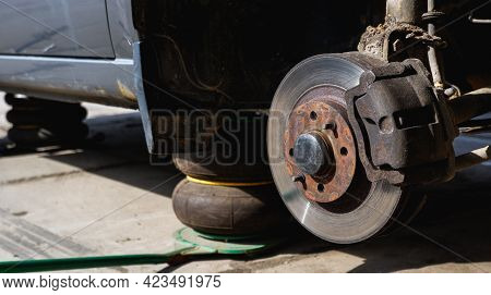 Automobile Fix. Car With Removed Wheels On Pneumatic Jacks. View Of The Brake Discs Hub.