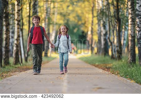 Primary School Pupils. Boy And Girl With Backpacks Walking Down In Park. Happy Children Happy To Go