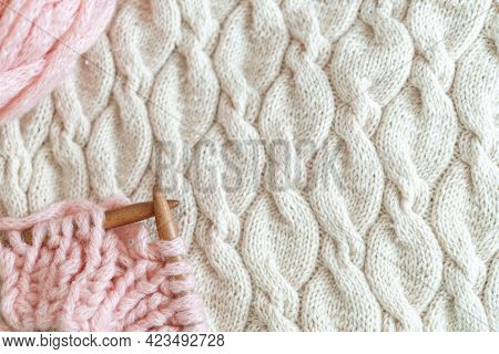 Wooden Knitting Needles Made Of Thick Wool Yarn On Background Knitted Blanket. Women's Hobby Knittin