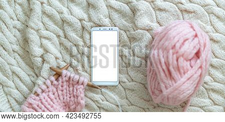 Smartphone With White Screen Lies On Knitted Blanket Next To Knitting, Wooden Needles And Thick Wool