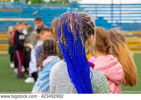 Young Girl With Fashionable Hairstyle With Braided Blue Ribbons In Her Hair, Blue Hair. Unusual Hair