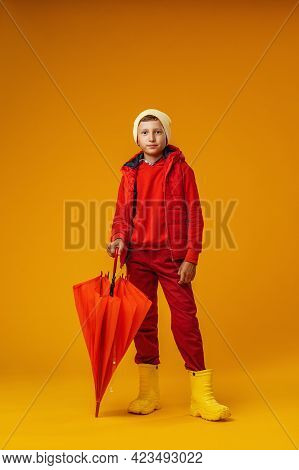 Happy Emotional Boy In Autumn Clothes With Orange Umbrella Stands On Yellow Background. Child Smiles