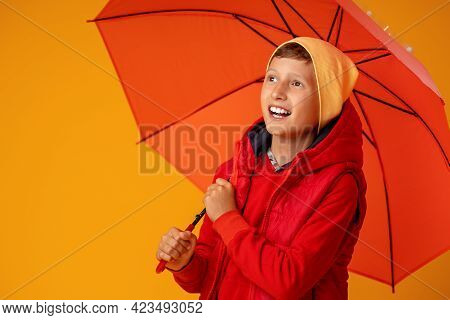 Happy Emotional Cheerful Boy In Autumn Clothes Laughing Under Orange Umbrella On Colored Yellow Back