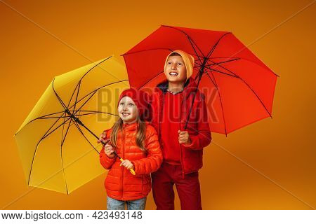Happy Emotional Children, A Boy And A Girl, In Autumn Clothes, Smiling And Hugging Standing Under Um