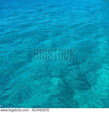 Sea Surface Turquoise Blue Color Background. Calm Crystal Clear Water With Small Ripples
