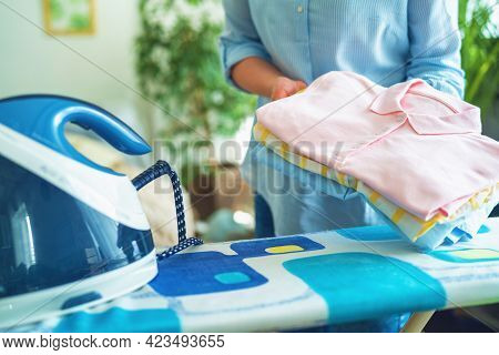 Close-up Of A Woman Ironing Clothes With An Iron On An Ironing Board At Home On A Sunny Day. Holds A