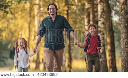 Father Walks With Children, Primary School Students, After School In Autumn Park. Beginning Classes.